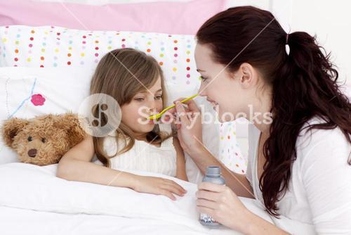 Little girl in bed taking syrup