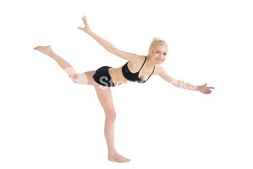 Sporty young woman balancing on one leg