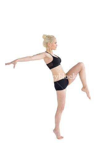 Sporty woman balancing on one leg while stretching out hands