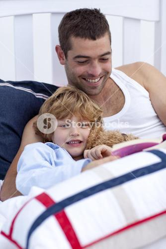 Dad and kid reading a book in bed