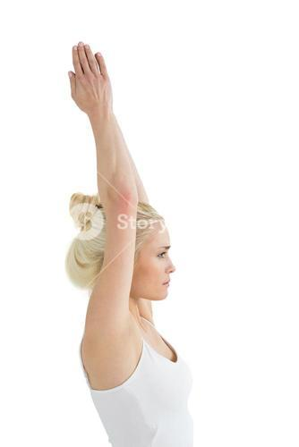 Toned woman with joined hands over head