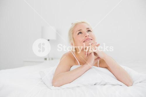 Young woman with joined hands lying in bed
