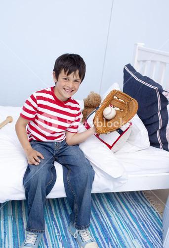 Smiling little boy playing baseball in bedroom