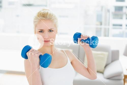 Woman with dumbbells at fitness studio