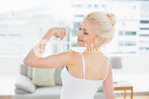 Rear view of fit woman flexing muscles in fitness studio
