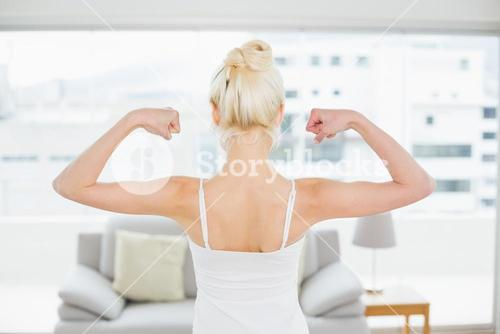Rear view of woman flexing muscles in fitness studio