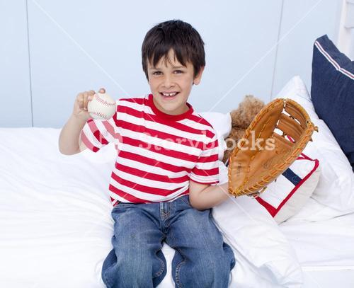 Happy little boy playing baseball in bed