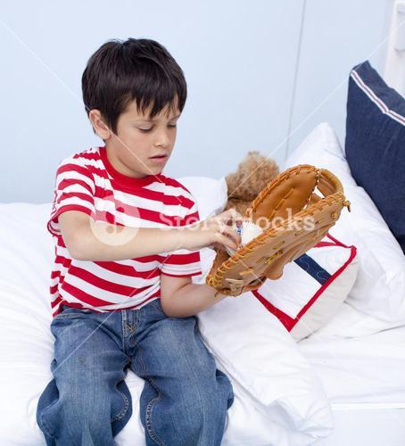 Little kid playing baseball in bed