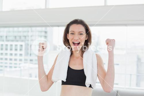 Cheerful woman clenching fists in fitness studio