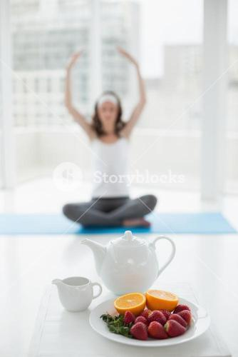 Blurred woman in meditation posture with healthy food in foreground