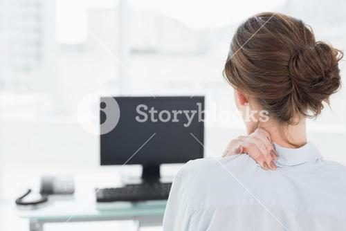 Rear view of a businesswoman with neck pain in office