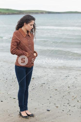 Cute young woman in stylish brown jacket on beach