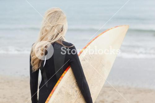 Rear view of woman in wet suit holding surfboard at beach