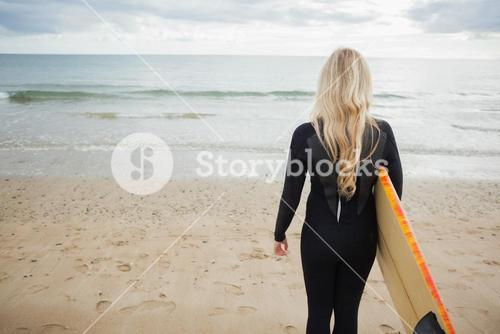 Rear view of woman in wet suit with surfboard at beach