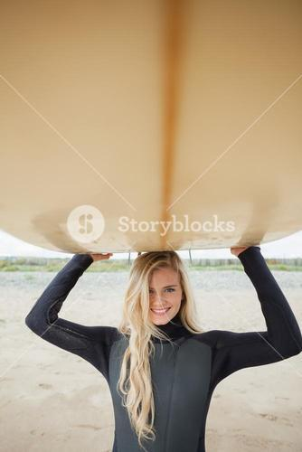 Smiling woman in wet suit holding surfboard over head at beach