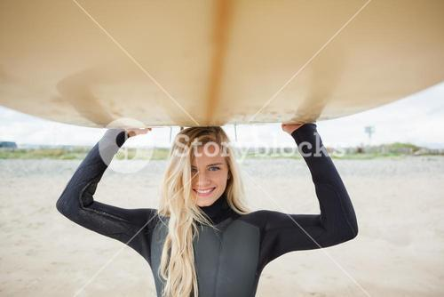 Smiling woman in wet suit holding surfboard over head