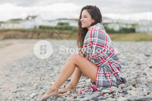 Smiling woman covered with blanket at the beach