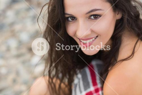 Smiling young woman covered with blanket at beach
