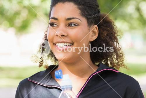 Close up of a smiling tired woman with water bottle in park