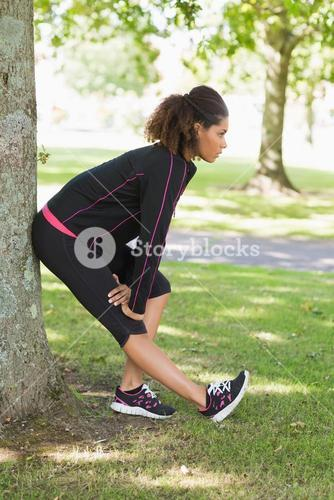 Healthy woman stretching her leg during exercise at park