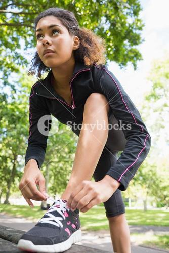 Sporty young woman wearing shoes in park