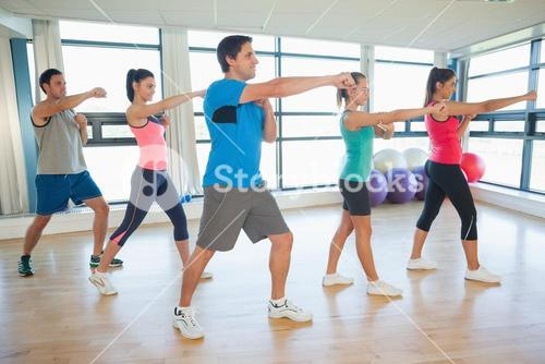 Sporty people doing power fitness exercise at yoga class