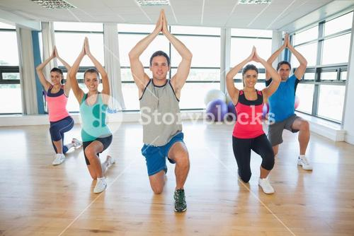 Fitness class and instructor kneeling in Namaste position