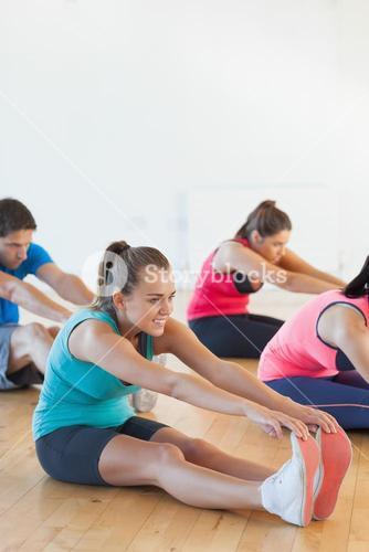 Class and instructor stretching legs in exercise room