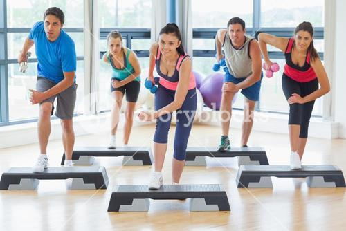 Instructor with fitness class performing step aerobics exercise with dumbbells