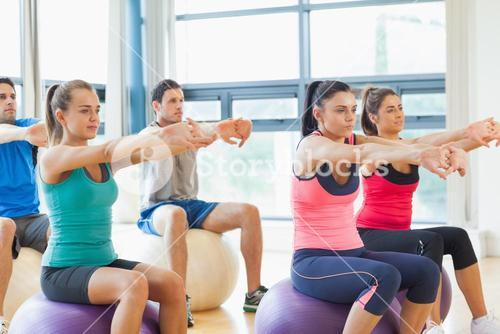 Sporty people stretching out hands on exercise balls at gym