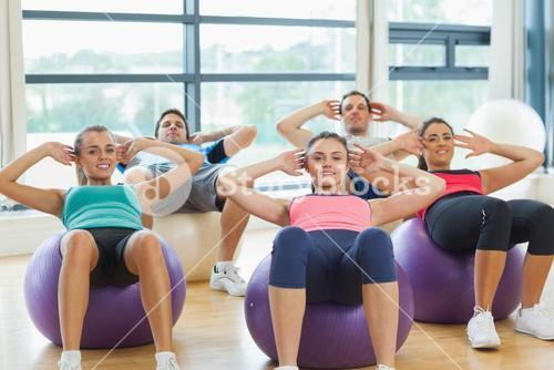Class doing abdominal crunches on fitness balls