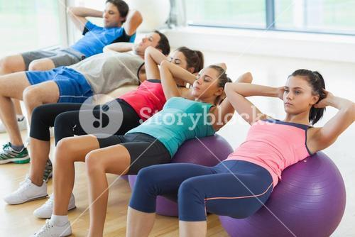 Class doing abdominal crunches on fitness balls in row