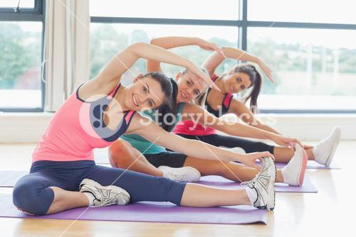 Fitness class and instructor doing stretching pilate exercises