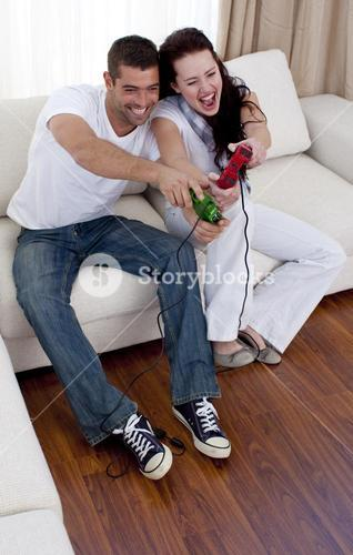 Couple having fun playing video games in livingroom