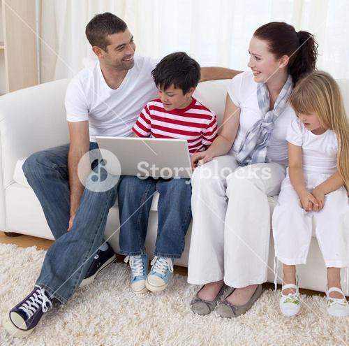Smiling family in livingroom using a laptop