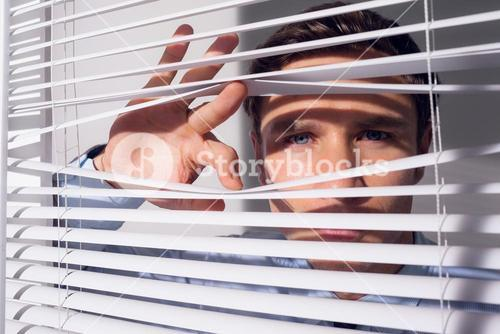 Businessman peeking through blinds