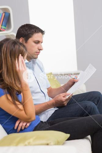 Stressed couple paying their bills at home