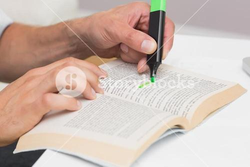Hands highlighting text in book on the table