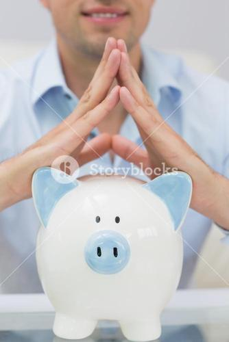 Closeup mid section man with piggy bank at home