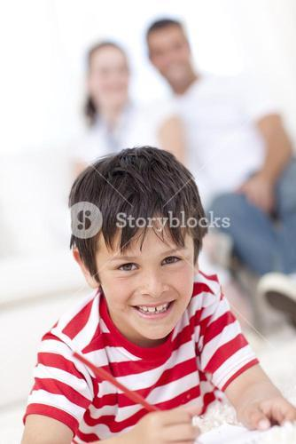 Smiling kid painting on floor in livingroom