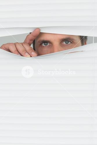 Green eyed businessman peeking through blinds