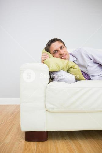 Smiling young businessman lying on sofa in living room