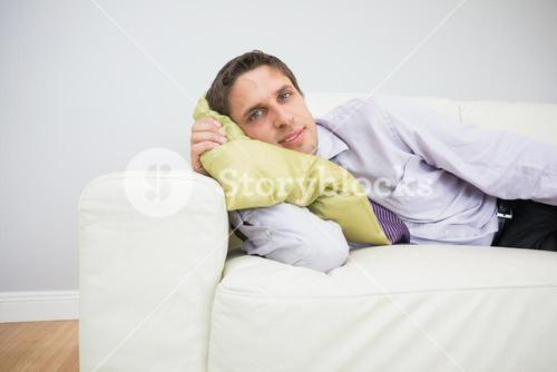 Portrait of a businessman lying on sofa in living room