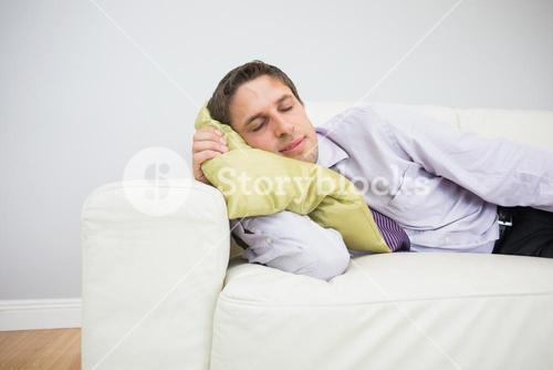 Tired businessman sleeping on sofa in living room
