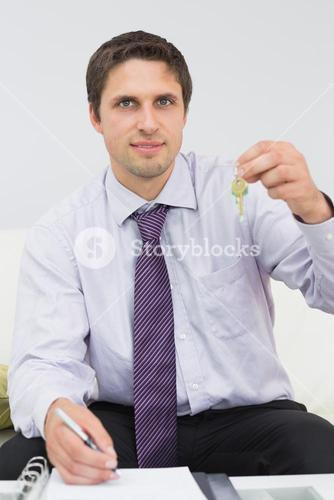 Businessman with documents holding up keys