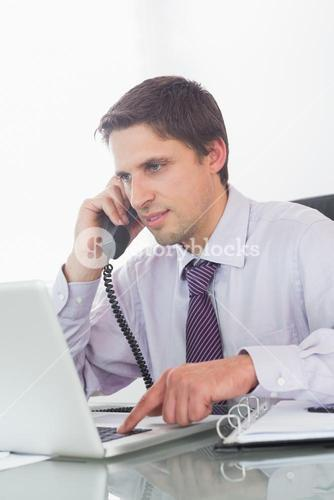 Businessman using telephone and laptop at desk