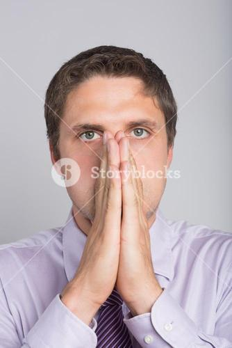 Green eyed businessman with hands covering face