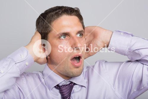 Green eyed businessman with hands covering ears