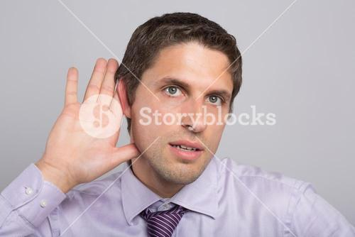 Closeup of a green eyed businessman with hand to ear