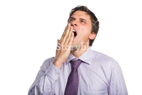 Young businessman in shirt and tie yawning
